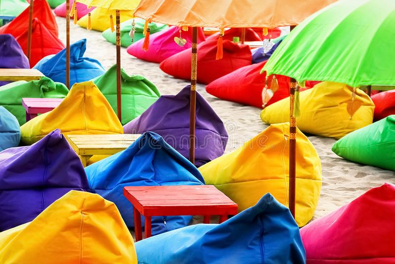 Guarda-chuvas, otomanos e tabelas de praia brilhantes coloridos no café da praia Fundo colorido do verão fotos de stock