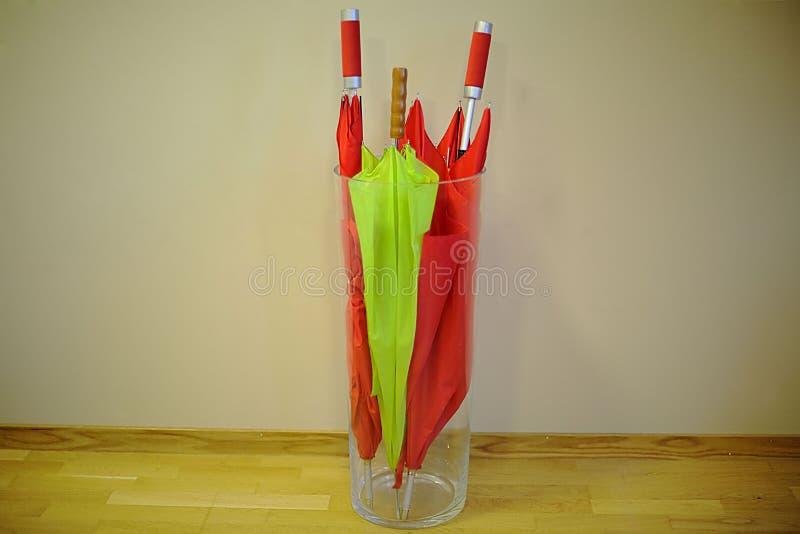Guarda-chuvas vermelhos e verdes no vaso de vidro grande, projeto da casa Projeto do escritório fotos de stock royalty free