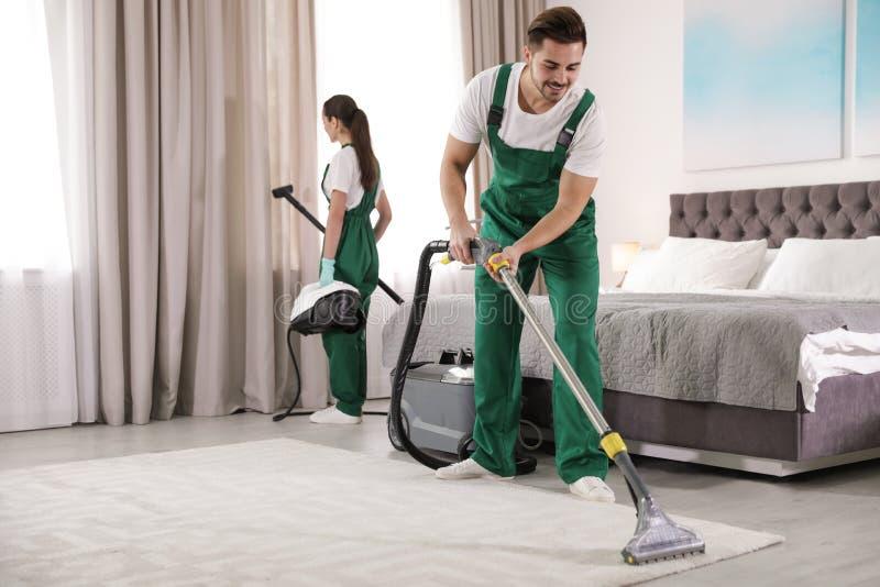 Guarda de serviço que limpam o quarto com o equipamento profissional fotografia de stock