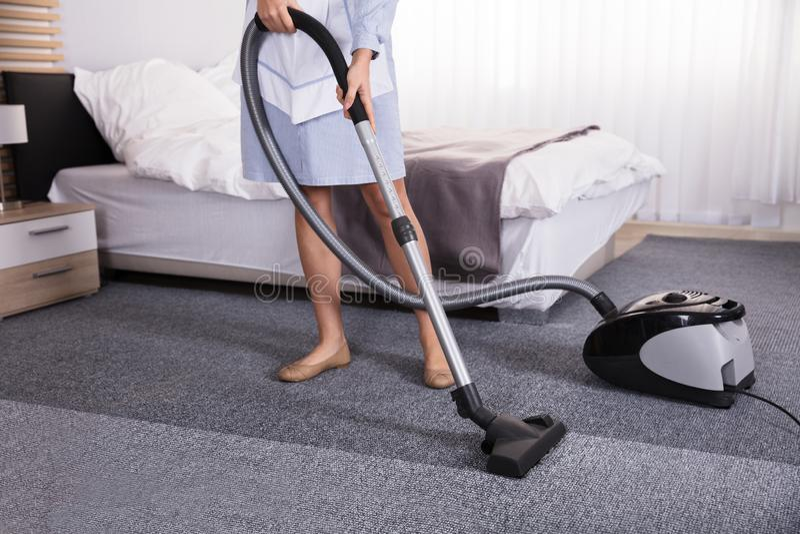 Guarda de serviço Using Vacuum Cleaner para o tapete de limpeza fotos de stock