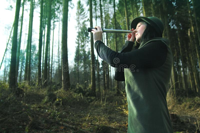 A guarda florestal explora a floresta com telescópio pequeno fotos de stock