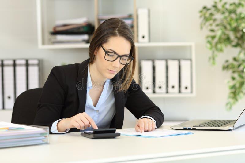 Guarda-livros que faz a contabilidade no escritório imagens de stock royalty free