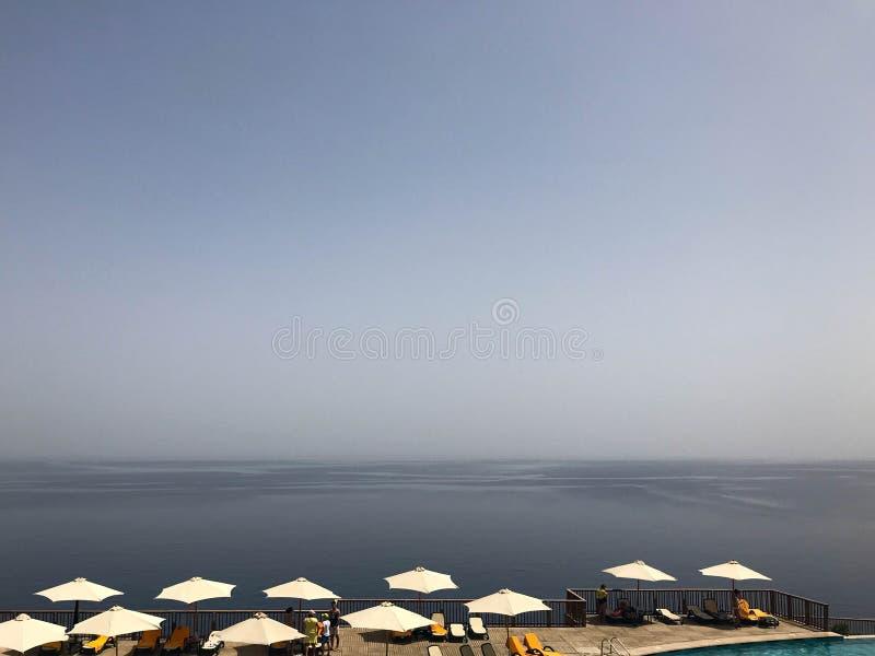 Guarda-sóis da luz do sol no hotel em um recurso exótico tropical, termas em uma montanha alta do montanhês acima do mar azul Vac fotos de stock