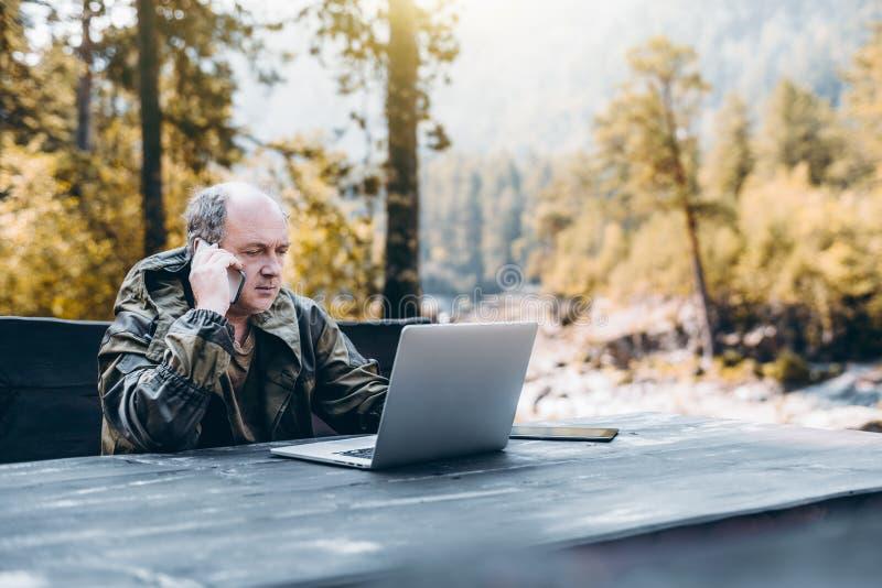 Guardabosque adulto con el ordenador portátil y el smartphone imagen de archivo