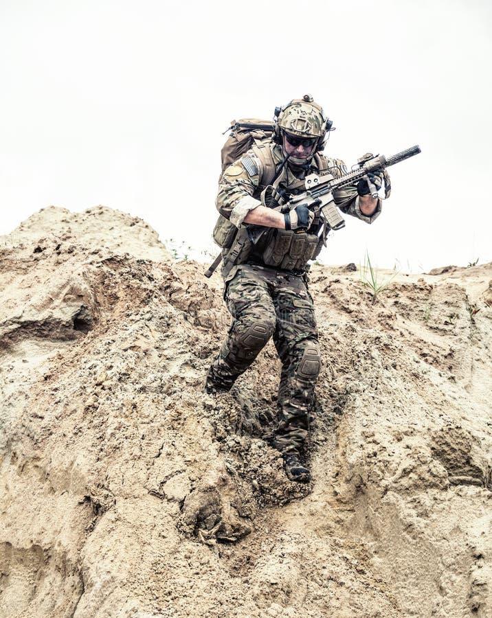Guardabosques del ejército con los brazos que corren abajo de la duna de arena foto de archivo