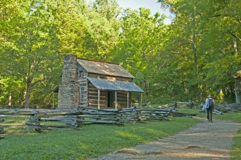 Guardabosques que camina a una cabaña de madera vieja. foto de archivo libre de regalías