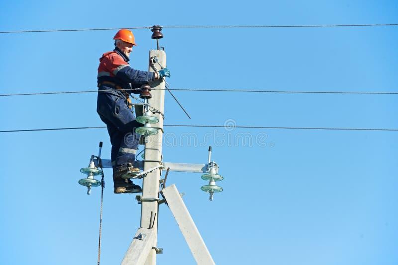 Guardalinee dell'elettricista di potenza sul lavoro sul palo fotografie stock