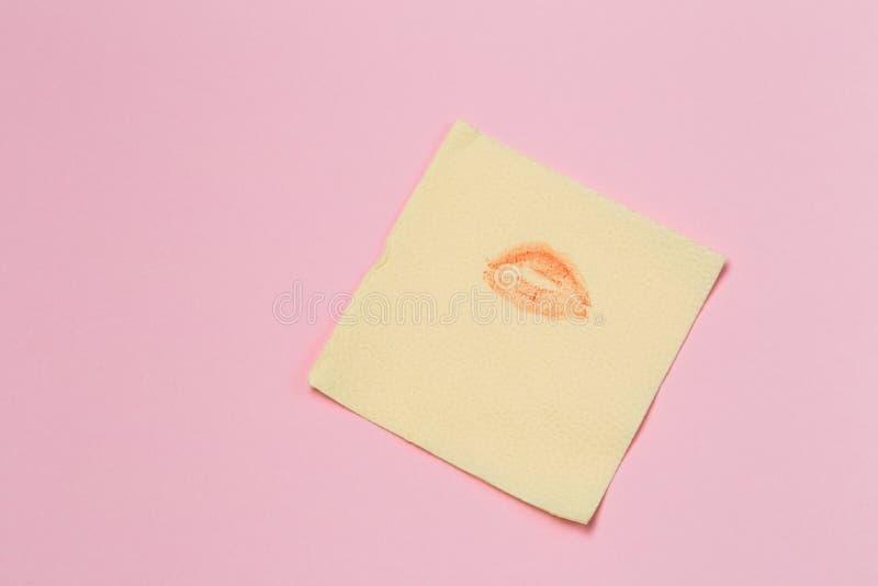 Guardanapo amarelo com um beijo no fundo cor-de-rosa fotografia de stock royalty free