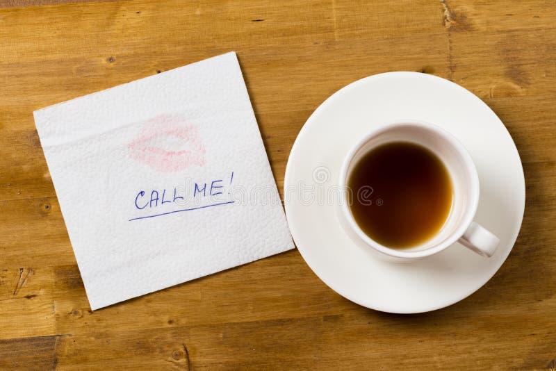 Guardanapo com um copo do beijo e de café no fundo de madeira foto de stock