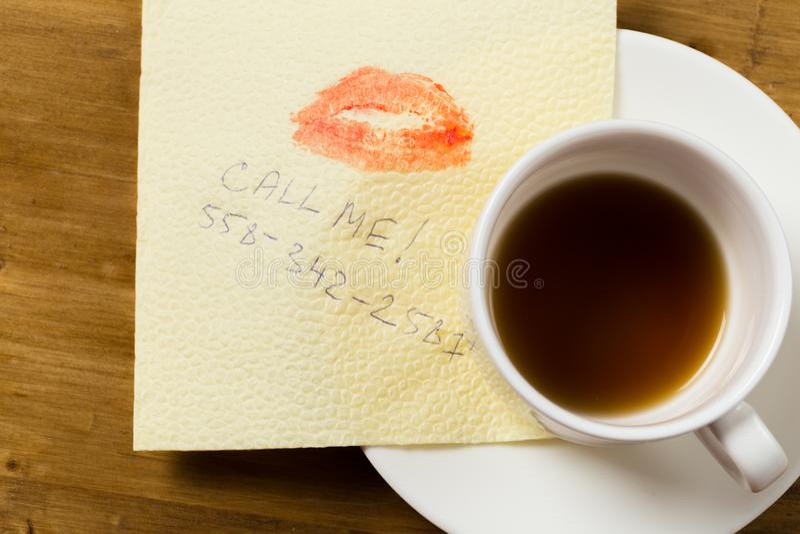 Guardanapo com um copo do beijo e de café no fundo de madeira foto de stock royalty free