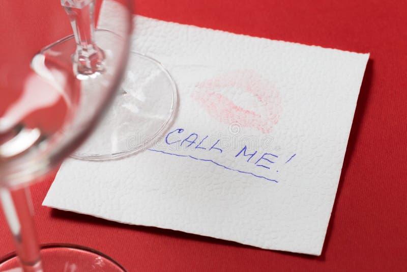 Guardanapo de papel com um beijo e um copo de vinho no fundo vermelho fotos de stock royalty free