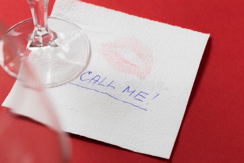Guardanapo de papel com um beijo e um copo de vinho no fundo vermelho fotografia de stock