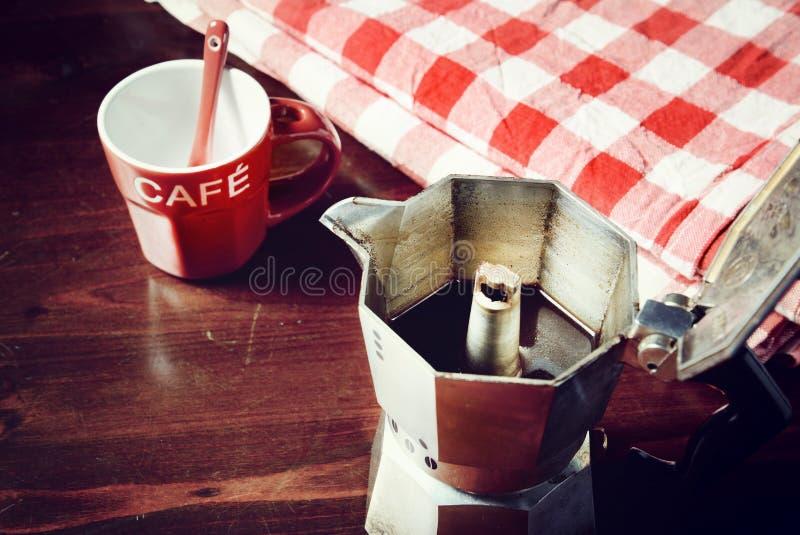 Guardanapo quadriculado na tabela de madeira com o copo de café vermelho fotografia de stock