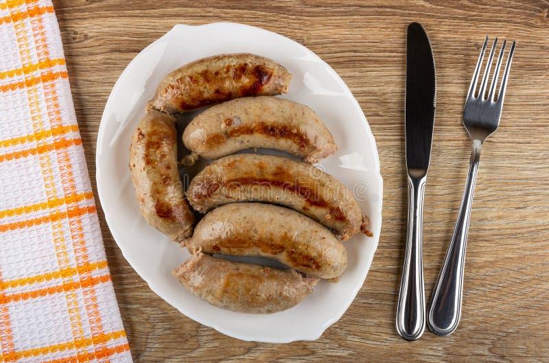 Guardanapo, salsichas do frango frito no prato branco, faca, forquilha na tabela de madeira Vista superior foto de stock royalty free