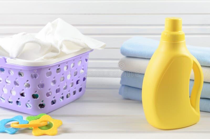 Guardanapo sujos do bebê em uma cesta de lavanderia roxa plástica, fol limpo foto de stock royalty free