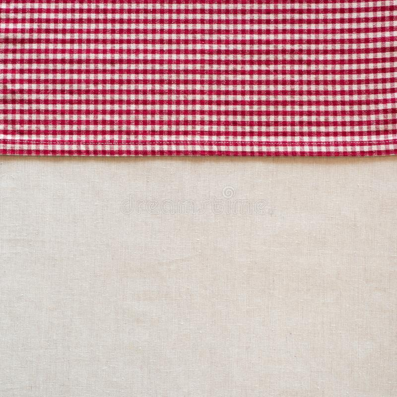 Guardanapo verificado vermelho e branco do estilo country de pano ao longo do lado da toalha de mesa de linho fora branca como o  imagens de stock