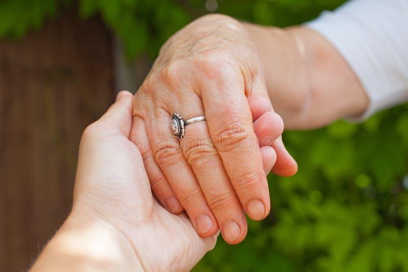 Guardando as mãos, doença de Parkinson fotos de stock