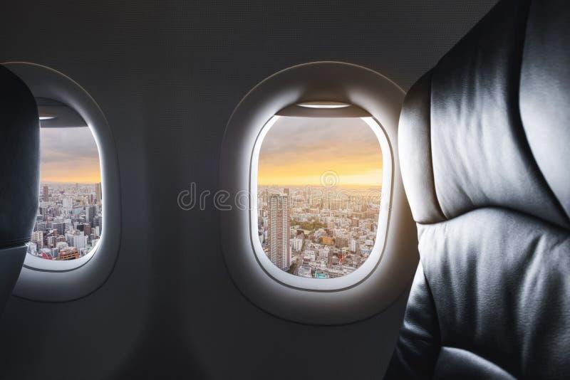 Guardando attraverso la finestra dell'aeroplano con la vista aerea della città di Osaka nel Giappone e della luce solare nel tram fotografia stock libera da diritti