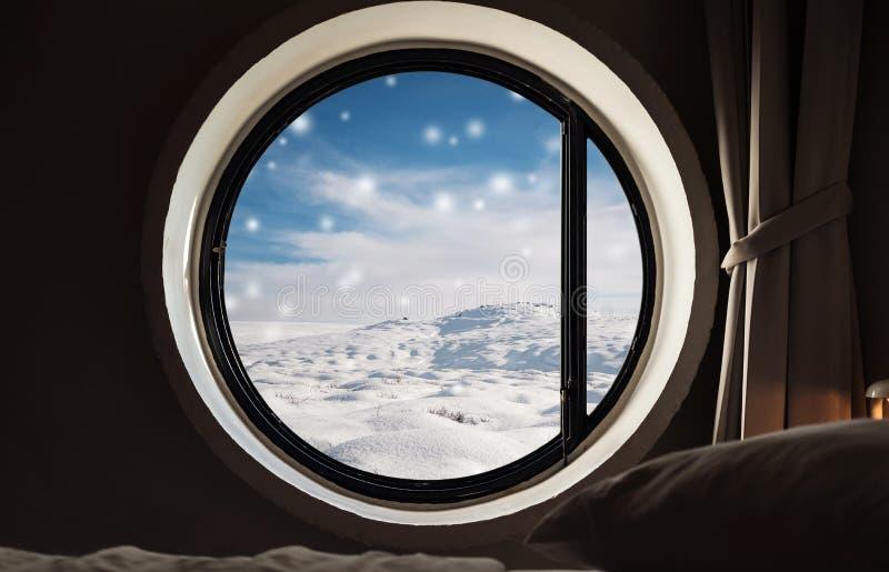 Guardando attraverso la finestra nell'inverno, cumulo di neve con la caduta della neve nell'inverno Mattina di natale fotografia stock libera da diritti