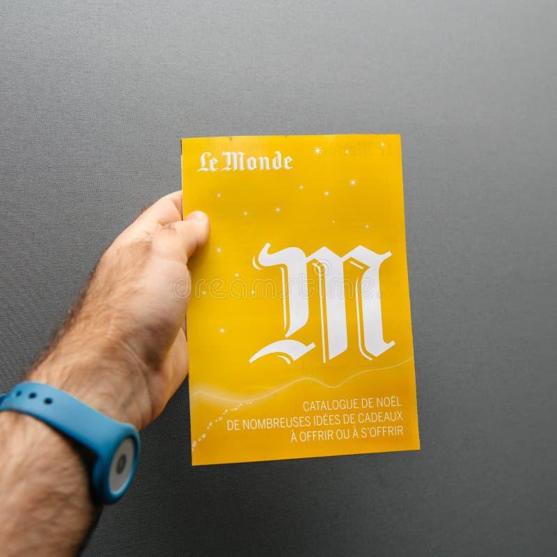 Guardando o catálogo amarelo do presente do Natal de Le Monde imagens de stock