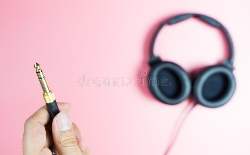 Guardando o jaque dourado do fones de ouvido no rosa imagens de stock royalty free