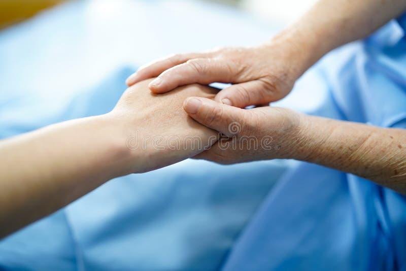 Guardando o paciente superior das m?os tocantes ou idoso asi?tico da mulher da senhora idosa com amor, o cuidado, ajudando, incen fotografia de stock royalty free