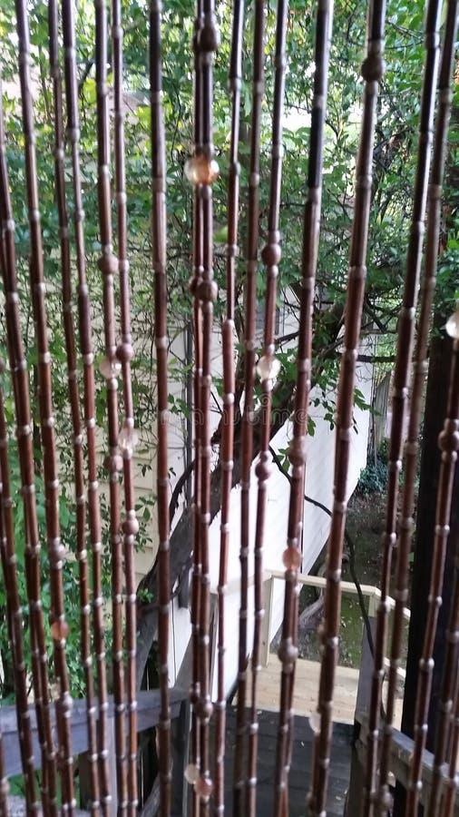 Guardando tramite le tende di bambù immagine stock libera da diritti