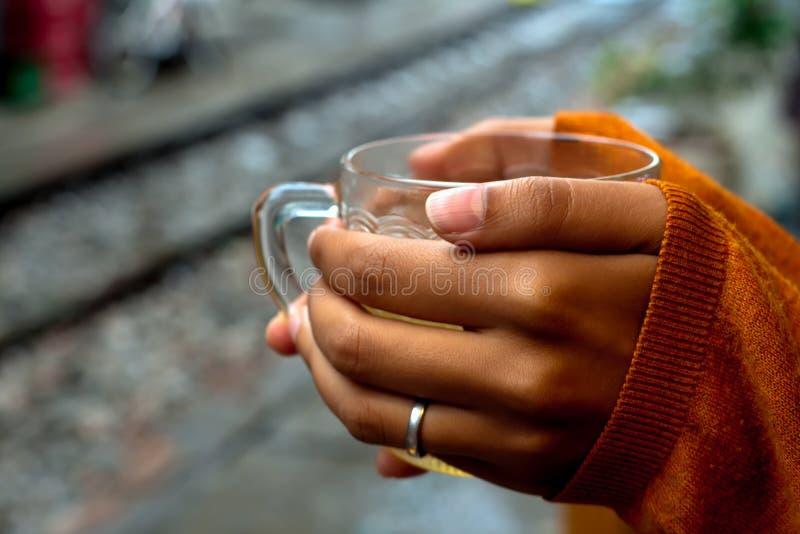 Guardando um copo do ch? pelo pul?ver dos trilhos que cobre as m?os por um ter?o imagem de stock royalty free