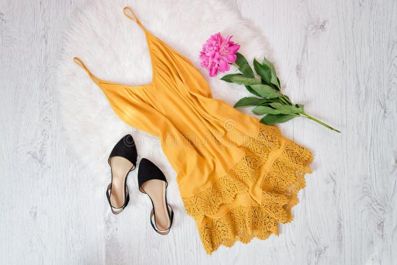 Guardapolvo anaranjado con el cordón y zapatos, peonías en la piel blanca concepto de moda imagenes de archivo