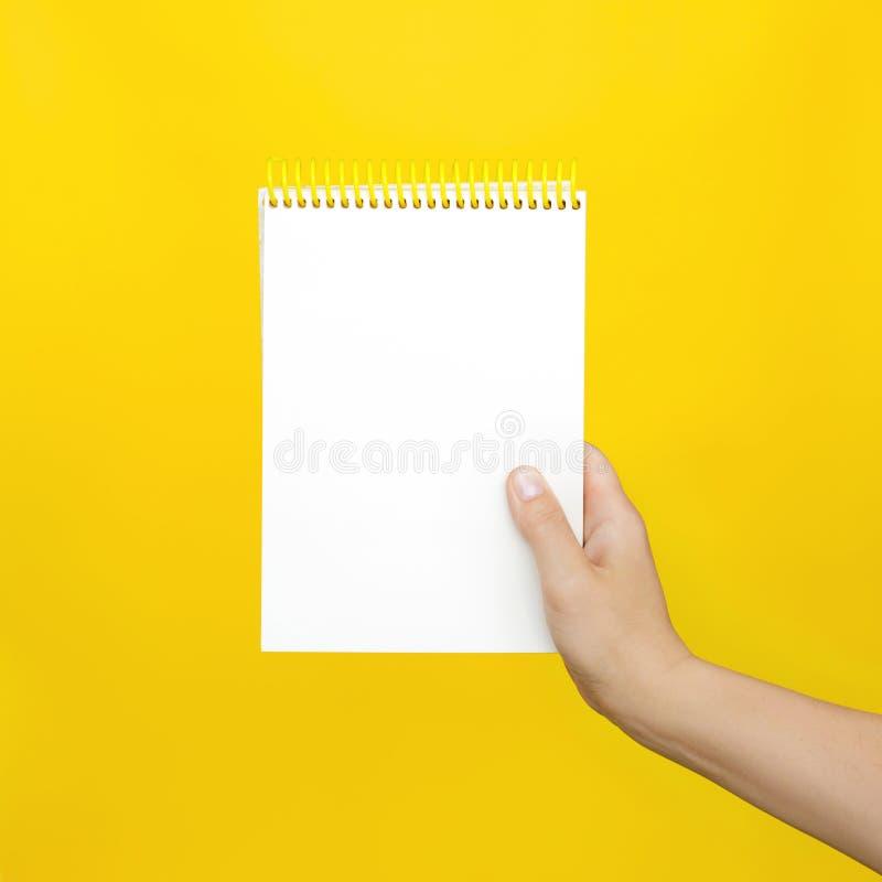 Guardar fêmea das mãos abre um bloco de notas vazio para notas no fundo amarelo foto de stock royalty free