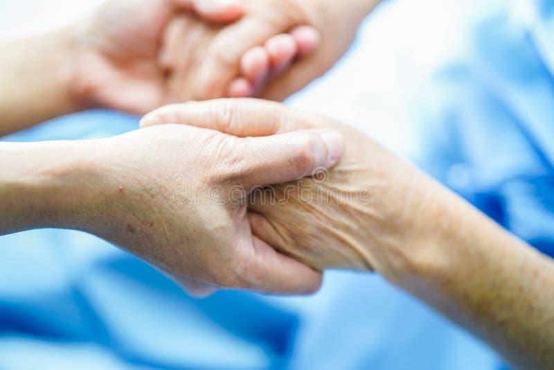 Guardar o paciente superior das m?os ou idoso asi?tico da mulher da senhora idosa com amor, cuidado, incentiva e empatia na divis imagem de stock