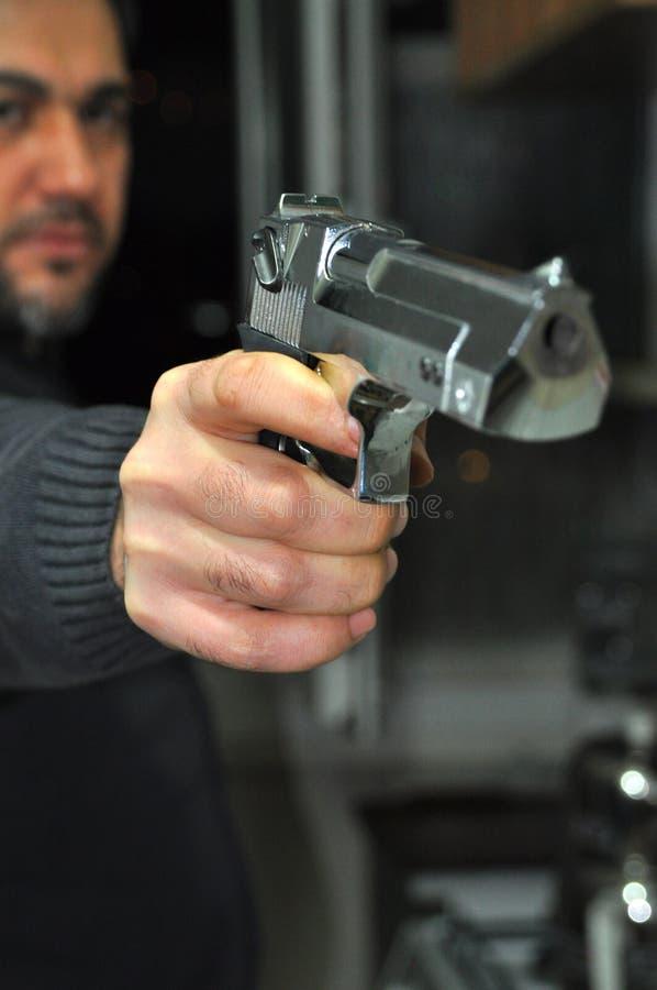 Guardarando uma arma da mão fotografia de stock