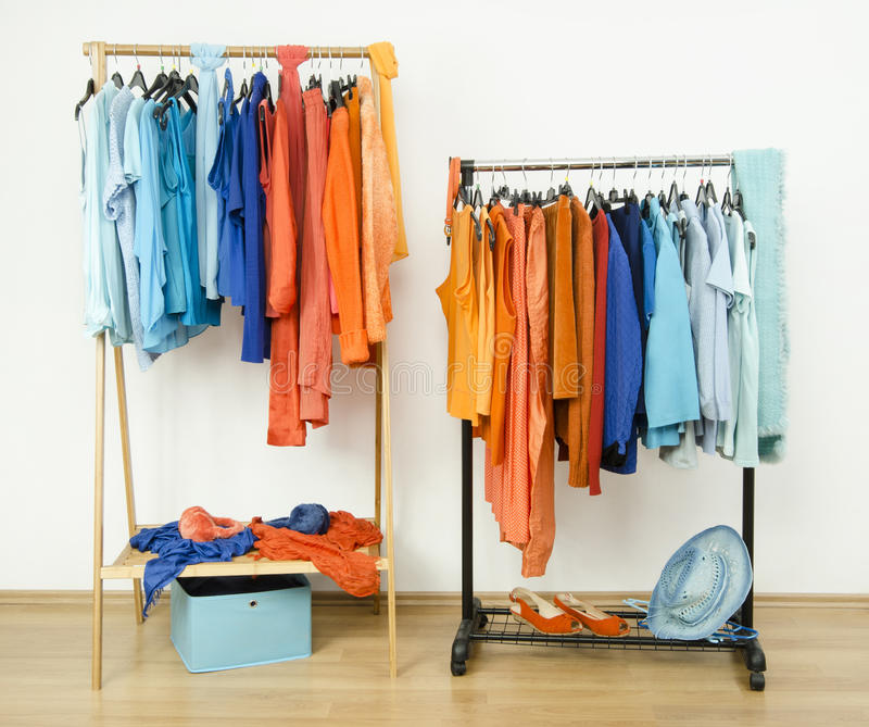 Guardaroba con i colori complementari arancio e vestiti blu sui ganci immagine stock libera da diritti