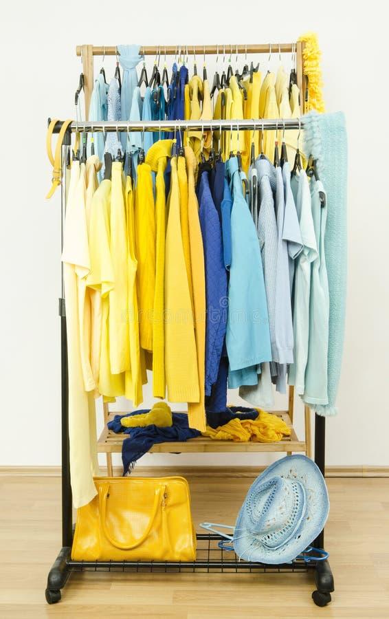 Guardaroba con le tonalità dei vestiti gialli e blu sui ganci immagini stock