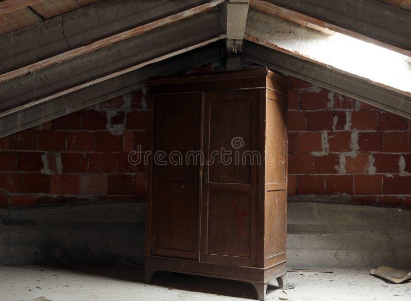 Guardaroba di legno nella soffitta disabitata polverosa immagini stock
