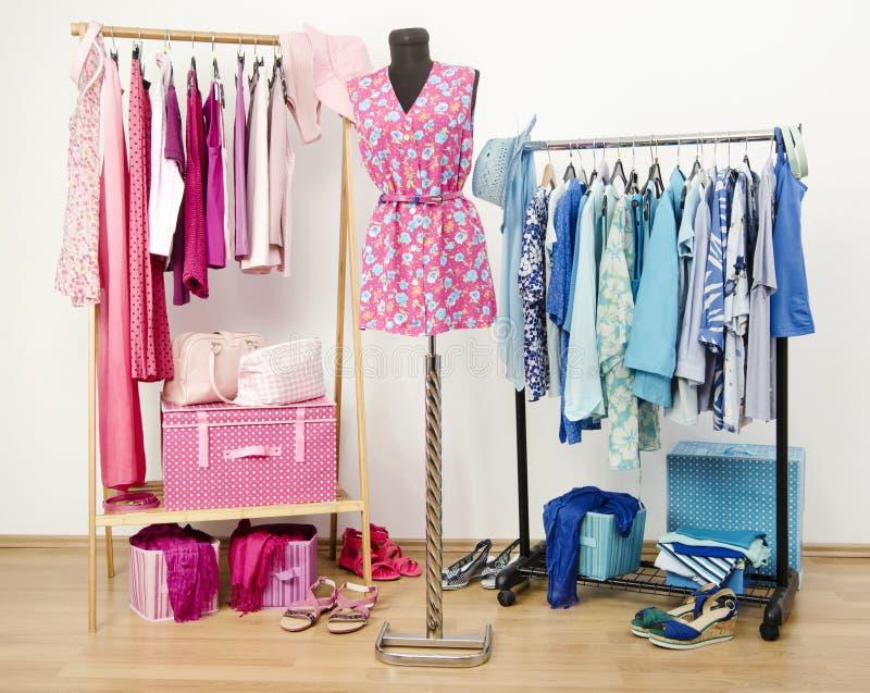 Guardaroba in pieno di tutte le tonalità dei vestiti, delle scarpe e degli accessori blu e rosa. immagine stock