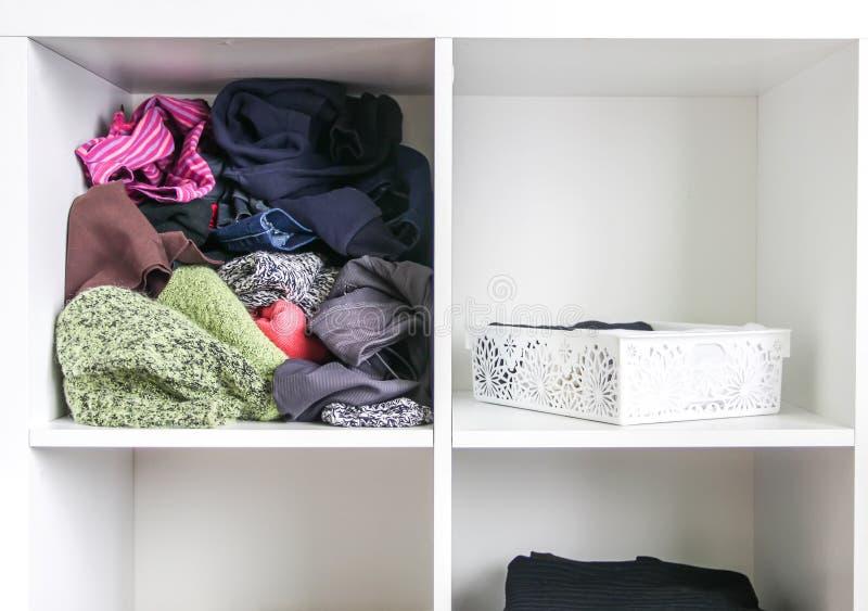 Guardarropa casero con diversa ropa Peque?a organizaci?n del espacio El contraste del orden y del desorden fotografía de archivo