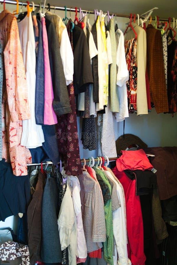 Guardarropa de la mujer con ropa colgante imagen de archivo