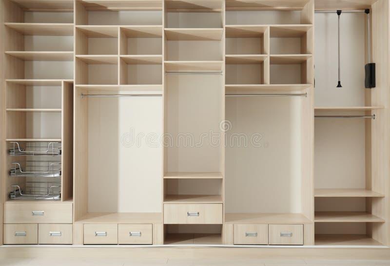 Guardarropa de madera vacío con los estantes y los cajones imagen de archivo
