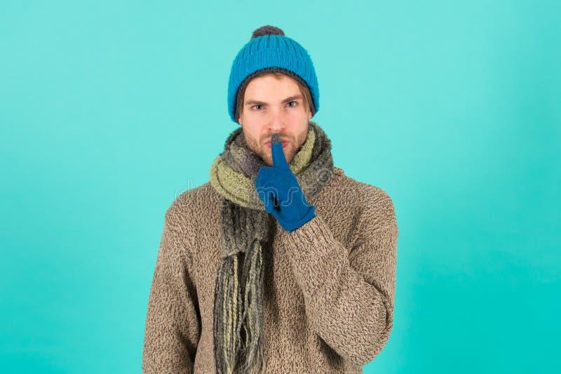 Guarde mi secreto Hombre guapo y sin afeitarse lleva accesorios de invierno con fondo azul Venta de la temporada de invierno Hipó foto de archivo libre de regalías