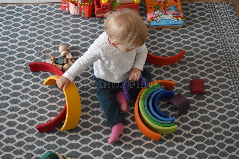 Guardería - bebé que juega con el arco iris de madera imagenes de archivo