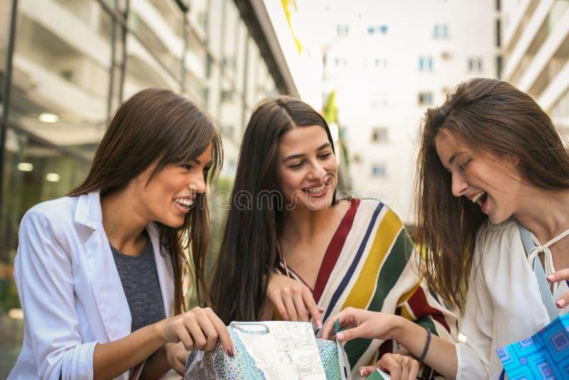 Guardi che cosa compriamo Tre giovani donne fotografia stock