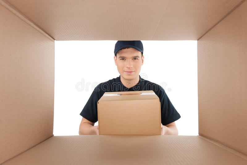 Guardi dalla scatola di cartone. Giovane tenuta allegra del fattorino immagini stock libere da diritti