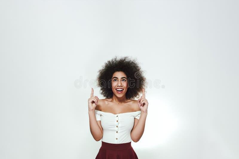 Guardi là! Donna afroamericana allegra e bella con capelli ricci che indica le dita su mentre stando contro fotografia stock libera da diritti