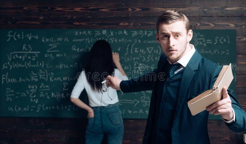 Guardi là Uomo dell'insegnante in vetri con il punto del manuale alla retrovisione della studentessa La donna scrive l'equazione  immagine stock