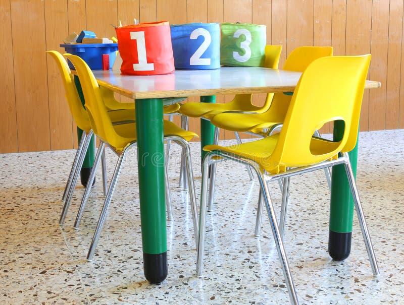 Guardia con i barattoli numerati e le piccole sedie gialle immagine stock libera da diritti