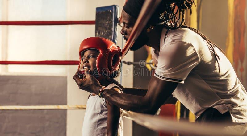 Guardia de la cabeza del boxeo del niño que lleva que se coloca dentro de un ring de boxeo foto de archivo