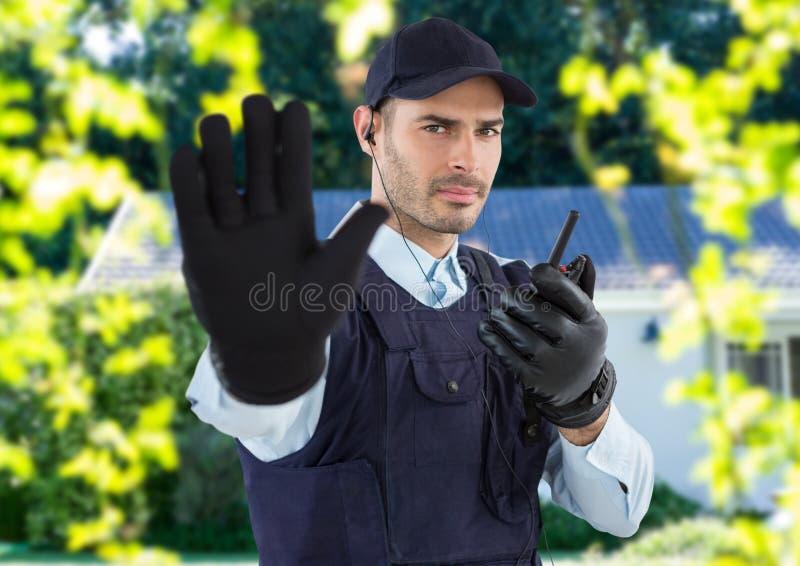 Guardia de seguridad con el sombrero, auricular y Walkietalkie, decir parada con su mano delante del hous imagenes de archivo