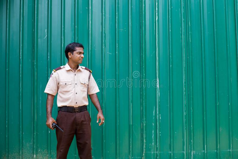 Guardia de seguridad del hotel en Sri Lanka contra una cerca verde foto de archivo
