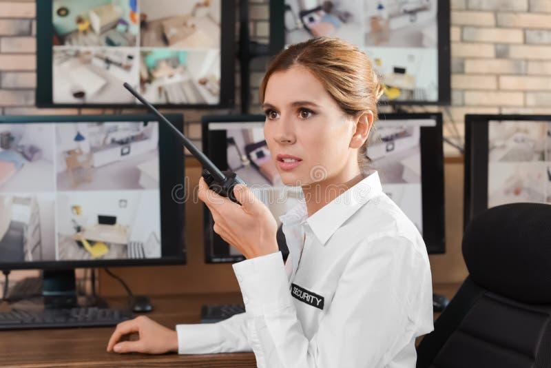 Guardia de seguridad femenino con el transmisor portátil en el lugar de trabajo imagenes de archivo